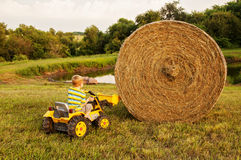 Boy on tractor lifting hay bale Royalty Free Stock Photos