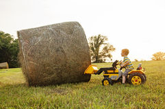 Boy on tractor lifting hay bale Stock Photos