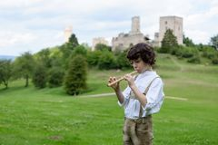 A boy in traditional Bavarian clothes. With a shepherd`s pipe on the background of ancient ruins Stock Photo