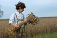A boy in traditional Bavarian clothes stands in the field. A boy in traditional Bavarian clothes stands in the field and holds a sheaf of rye in his hands Royalty Free Stock Photography