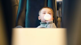 Boy in the train drinking milk from the bottle. Little boy in express train drinking milk from the bottle. View between two seats stock footage