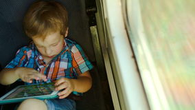 Boy in train using tablet computer. High angle view of a little boy sitting by the window in train and using touch pad stock video footage