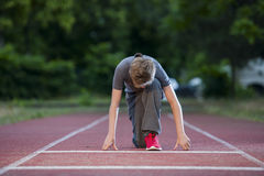 Boy trained deep start looking down. Deep frontal full-body view looking a young male teenagers in low-start position on a tartan track in the camera Royalty Free Stock Photo