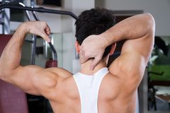 Boy training. Boy trainin his muscles in a gym Stock Image