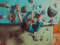 Boy training in climbing gym Stock Images