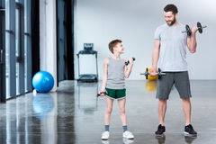 Boy training with dumbbells together with coach stock images