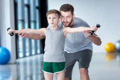 Boy training with dumbbells together with coach stock photo