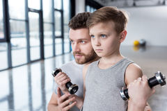 Boy training with dumbbells together with coach stock photos