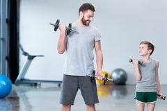 Boy training with dumbbells together with coach Royalty Free Stock Photo