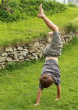 Boy training handstand. Exercising barefoot little boy in grey t-shirt and shorts training a handstand on green grass Stock Photography