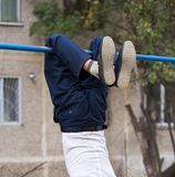 Boy training on a horizontal bar. In the park in nature Stock Image