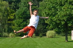 Boy on Trampoline. Boy jumping high on trampoline, in motion Royalty Free Stock Photo