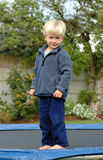 Boy on trampoline. A full body of a beautiful clever blond caucasian white boy child with cute and smart smiling expression in his handsome face standing Royalty Free Stock Photo