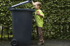 Boy Trashing A Can. Boy wanting to throw a can in the container, he is learning to be aware that recycling is important Royalty Free Stock Photo