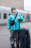 Boy with a travel bag near a train Royalty Free Stock Images