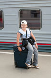Boy with travel bag near  train Stock Images