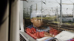 Boy travel in French train. FRANCE - CIRCa 2016: Handsome little boy looking out the fast train window to outside then reading a magazine while the French stock video footage