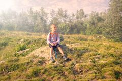 A boy traveler with a backpack and trekking poles is resting on a stone in the fog royalty free stock photo