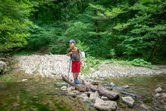 Boy traveler crosses the creek on a log royalty free stock photos
