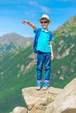 boy traveler stands on a rock and shows up royalty free stock image