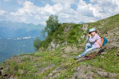 Boy-traveler with trecking poles in panama is resting on the top of the mountain royalty free stock image