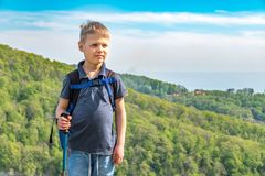 A boy traveler with trekking poles and a backpack stands on top of a mountain among green forest stock photos