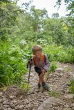 A boy traveler with a trekking poles climbs up a steep slope stock photos