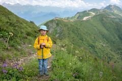 A boy traveler with trekking poles in a yellow raincoat and a panama is standing on the path to the top of the mountain range stock photography