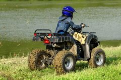 The boy is traveling on an ATV stock images