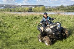 The boy is traveling on an ATV royalty free stock photography