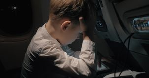 Boy traveling by plane and playing chess game on digital tablet. Child trying to entertain himself with chess game on tablet computer during night plane journey stock footage
