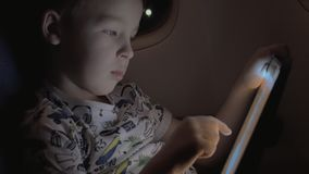 Boy traveling by plane and playing game on tablet PC. Slow motion shot of a child entertaining with game on digital tablet during his night air journey stock video footage