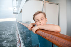 Boy traveling on ship and hold on handrails Stock Photos