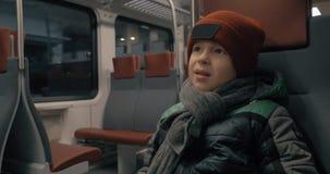 Boy traveling by suburban train. Boy sitting quietly in moving suburban train. Traveling in winter evening stock video footage