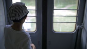 Boy traveling by train, slow motion. Have fun stock footage