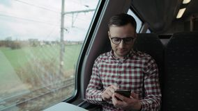 Boy traveling on the train and talking on a smartphone. 4K stock video footage