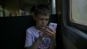 Boy travelling by train sitting in wagon using mobile phone, slow motion stock video