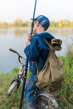 Boy travels with a backpack on the river bank Royalty Free Stock Images