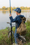 Boy travels with a backpack on the river bank Stock Image