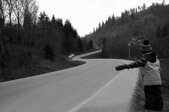 The boy travels hitchhiking in the mountains. In fall or winter Royalty Free Stock Photography