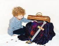 Boy with Treasure. Little boy (3) sitting next to a chest filled with treasure on a white background Royalty Free Stock Images
