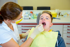 Boy is treated by female dentist Royalty Free Stock Images