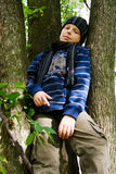 Boy on a Tree. Portrait of young schoolboy in a cap and scarf, sitting on a tree Stock Photography