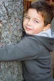 Boy with Tree. A five years old boy playing in his home`s garden Stock Photo