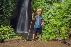 Boy with a trekking stick on the background of Leke Leke waterfall in Bali island Indonesia. Traveling with children. Concept stock images