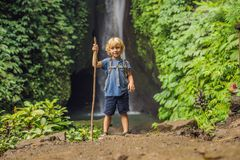 Boy with a trekking stick on the background of Leke Leke waterfall in Bali island Indonesia. Traveling with children. Concept royalty free stock photo