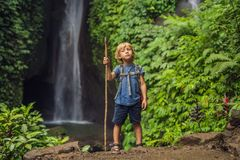 Boy with a trekking stick on the background of Leke Leke waterfall in Bali island Indonesia. Traveling with children. Concept royalty free stock images