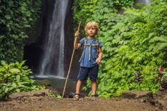 Boy with a trekking stick on the background of Leke Leke waterfall in Bali island Indonesia. Traveling with children concept stock photos