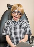 Boy With Trial Frame Making Funny Face At Optician Royalty Free Stock Image