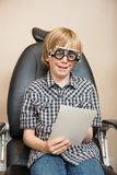 Boy With Trial Frame Reading Test Chart On Chair Stock Photos
